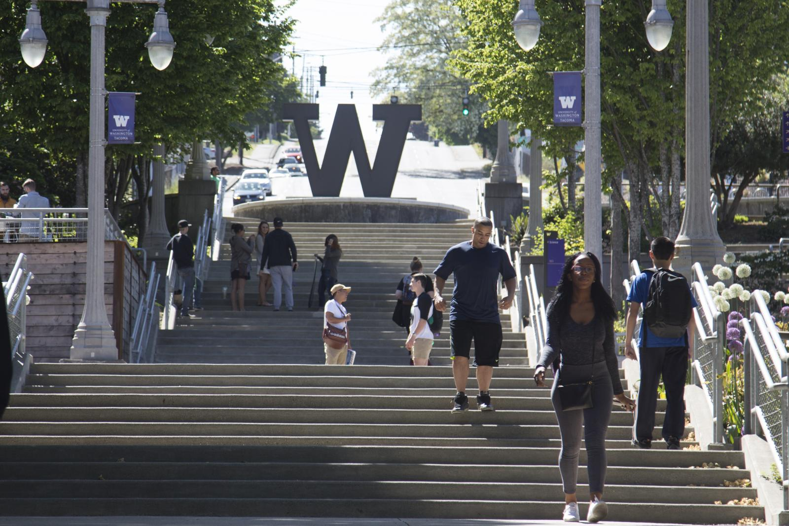 "The UW Tacoma campus stairs, showing ""W"" sculpture with students walking in front."
