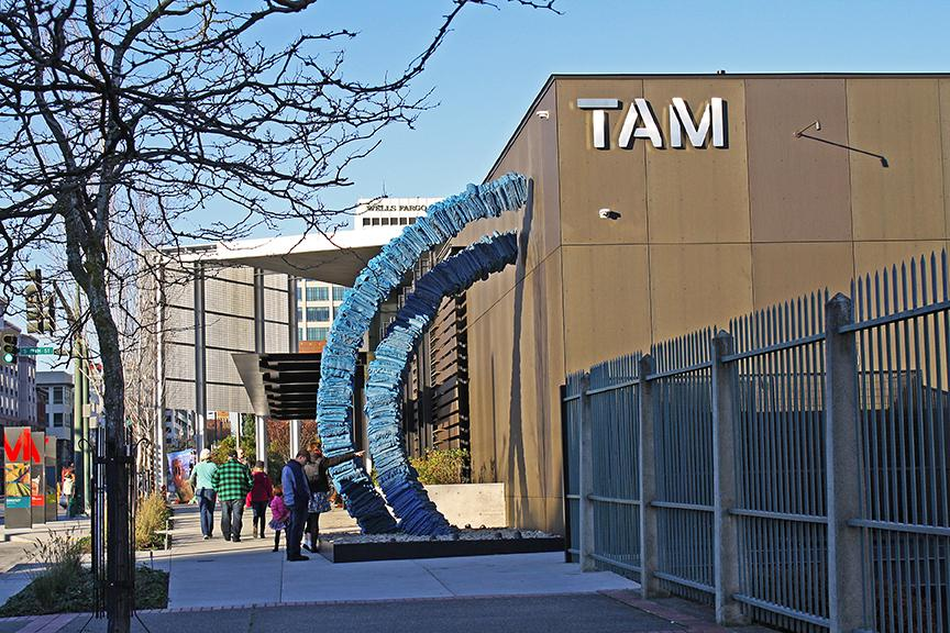 Blanket Stories along the TAM building on Pacific Avenue, showing two blue infinity loops comprised of bronze cast blankets