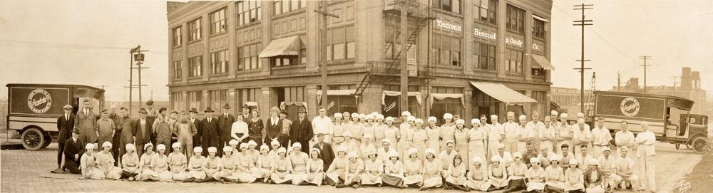 Photo of the employees of the Tacoma Biscuit and Candy Co. in 1921 Tacoma, WA who are posed in rows in front of the companys building.