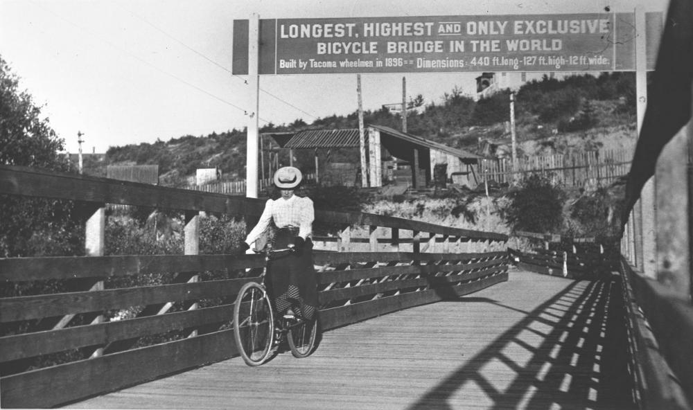 "Image showing a woman crossing a wooden bicycle bridge in 1900, with a sign above reading ""Longest, Highest, and Only Exclusive Bicycle Bridge in the World."""
