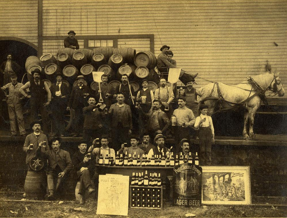 Group photo of employees of the Puget Sound Brewing Company in front of a wood frame building.